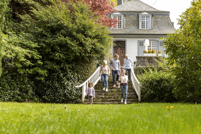 Extended family walking on stairs in garden of their home