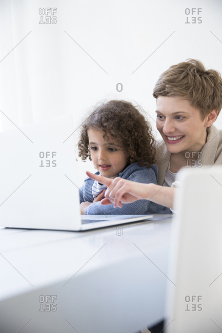 Smiling mother and son using laptop at home