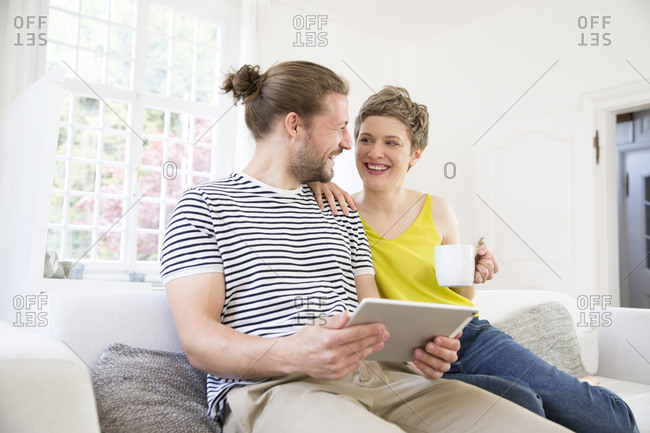 Happy young couple using tablet on couch at home