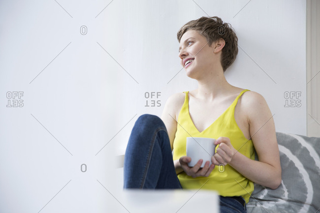 Smiling woman with cup of coffee at home