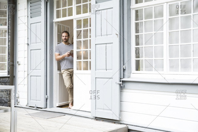 Young man with tablet standing at terrace door at home