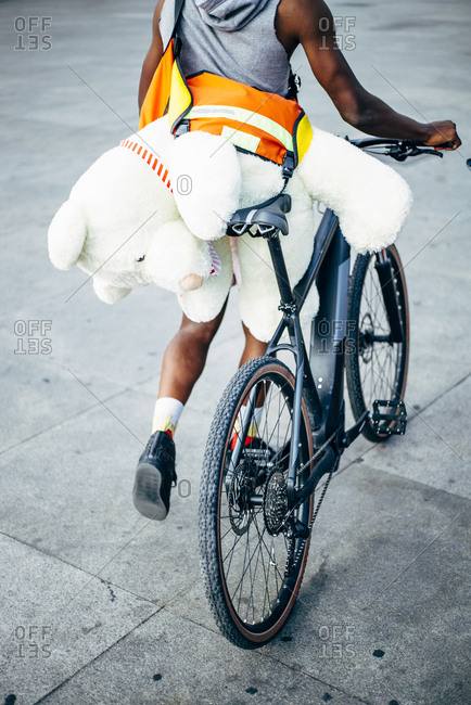 Bicycle courier delivering a teddy bear