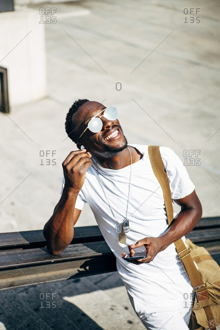 Happy young man with earphones and mobile phone in the city