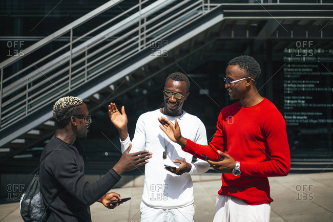 Three cool young men with cell phones meeting in the city