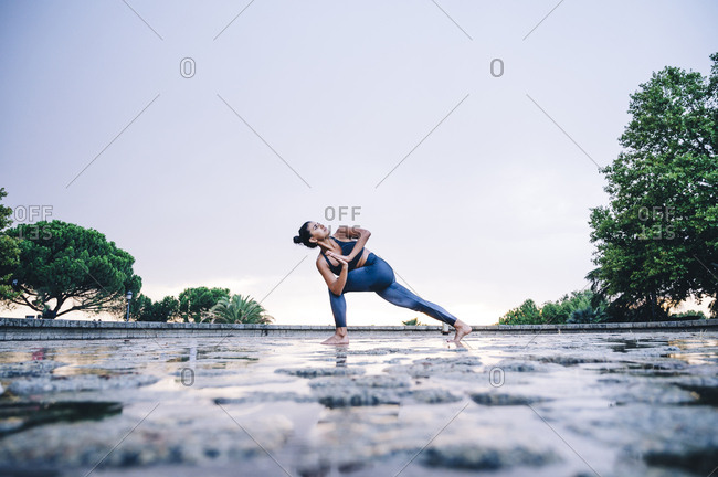Woman practicing yoga in the rain- triangle pose