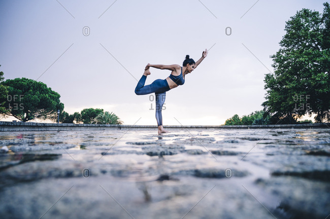 Woman practicing yoga in the rain- dancer position
