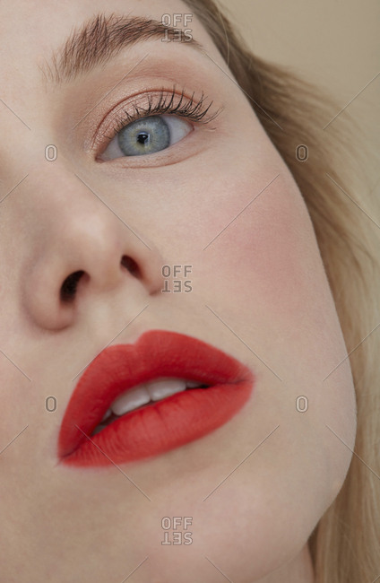 Woman's face with made up red lips- close-up