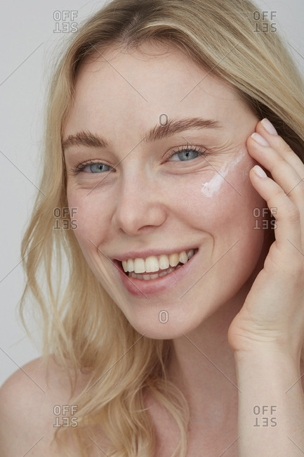 Portrait of smiling young woman applying cream on her face