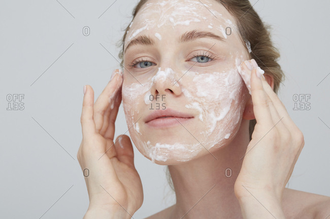Portrait of blond young woman applying cream on her face