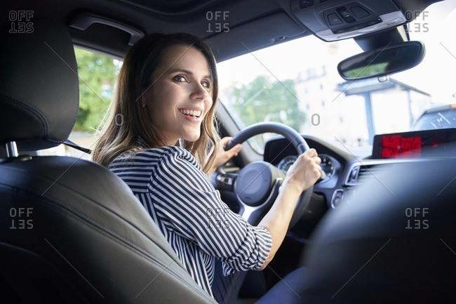 Happy woman driving car