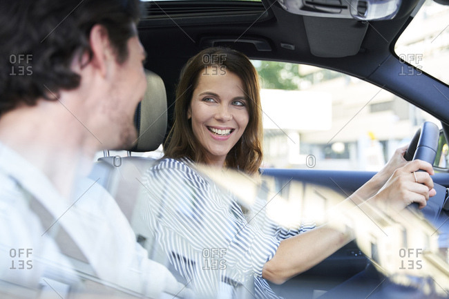 Happy couple in a car with woman driving