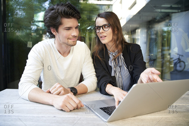 Businessman and businesswoman with laptop meeting in the city