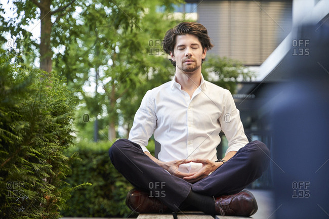 Businessman doing yoga on a bench in the city