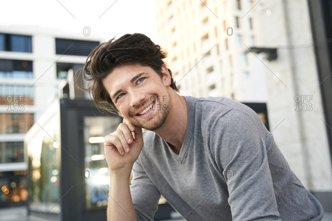 Portrait of smiling man wearing grey shirt in the city