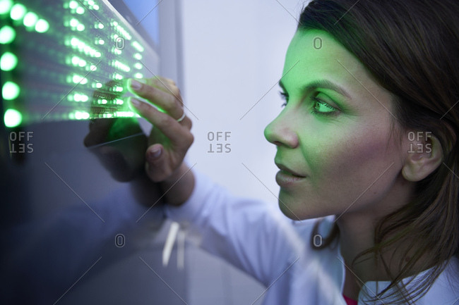 Close-up of woman touching green led touchscreen