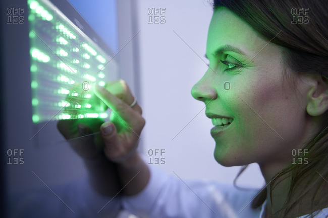 Close-up of smiling woman touching green led touchscreen