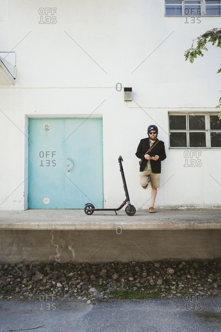 Man with Electric Scooter leaning against facade using smartphone