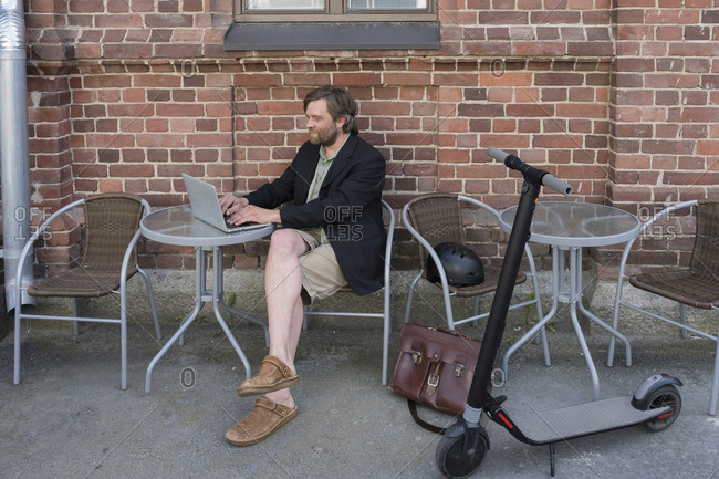 Man with Electric Scooter sitting at pavement cafe using laptop