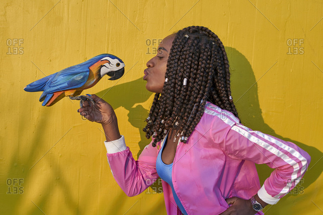 Woman kissing a wooden parrot on a yellow wall