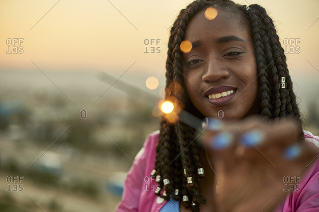 Woman with sparkler at sunset