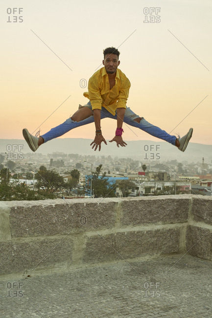 Young man in a yellow shirt jumping from a wall at sunset