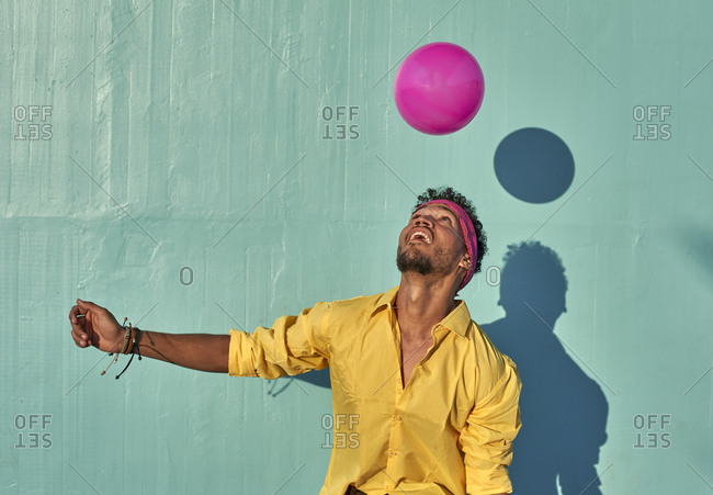 Young black man playing with a pink ball in front of a blue wall