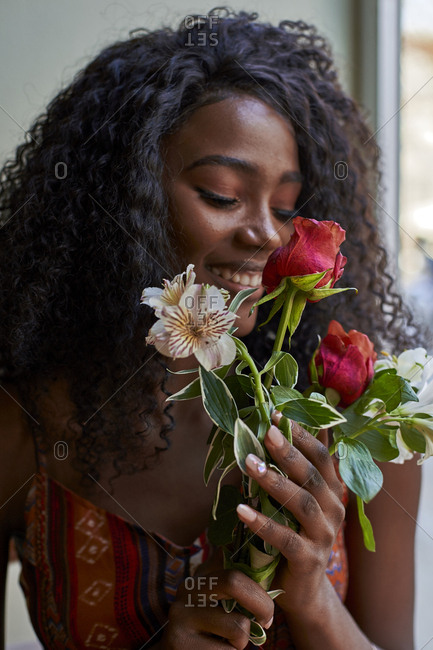Portrait of young African woman  smelling flowers and smiling in a cafe
