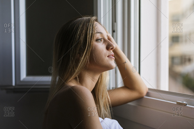 Young woman gazing out of hotel window