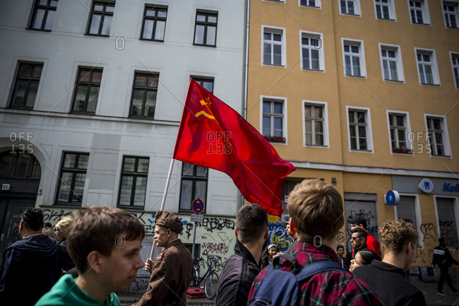 Berlin, Germany - May 1, 2019: An elderly man in military uniform carries a communist flag on May Day