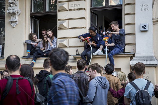 Berlin, Germany - May 1, 2019: People preparing beer funnels in a window on May Day