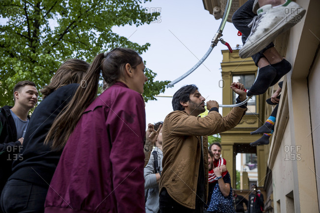Berlin, Germany - May 1, 2019: A man has a beer funnel on May Day