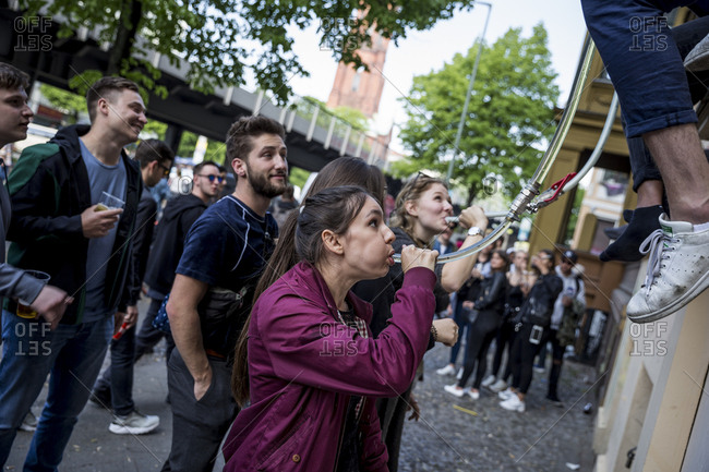 Berlin, Germany - May 1, 2019: A woman has a beer funnel on May Day