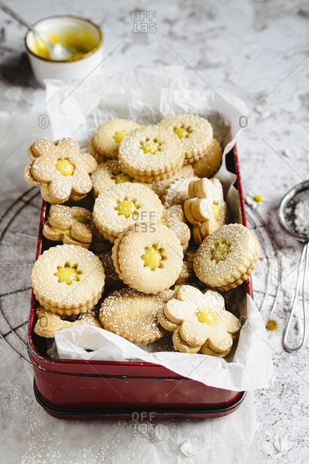 Lemon curd linzer cookies into a metal box