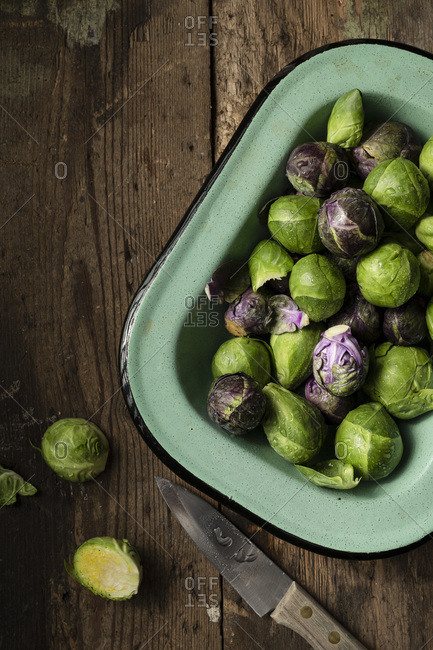 Raw Brussel sprouts in a vintage, green enamel dish, on a rustic wooden surface. A knife is alongside.