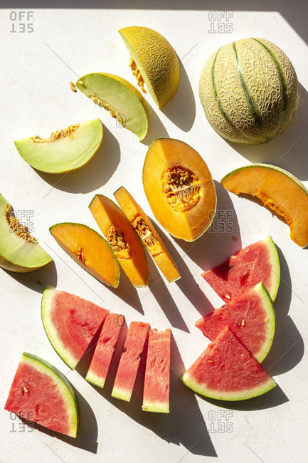 Slices of watermelon, cantaloupe and honeydew melon on the table, top view