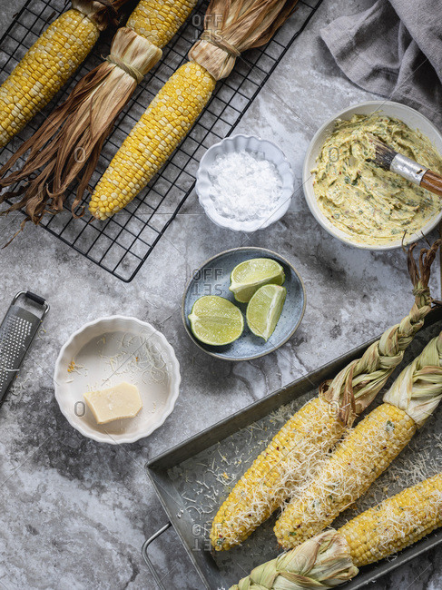 Mexican street corn on the cob seasoned and plain. Ingredients off to the side: herbed butter, lime, salt and cheese