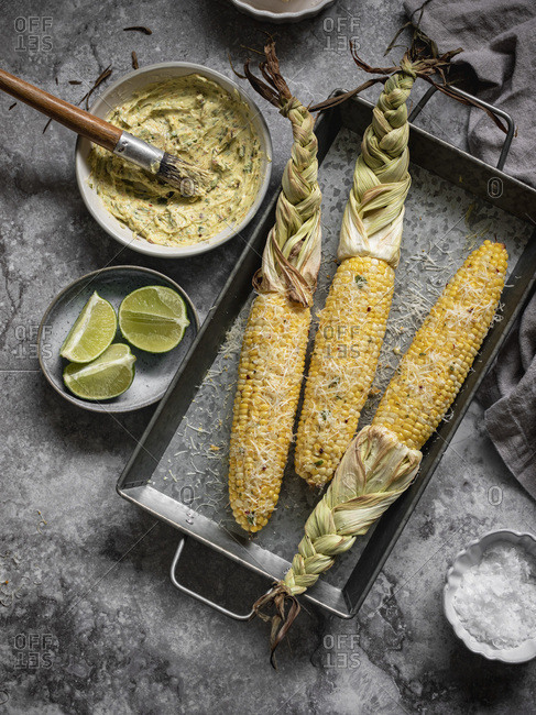 Mexican street corn on the cob. Ingredients off to the side: herbed butter, lime, salt and cheese