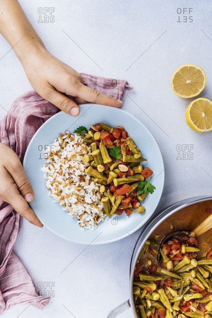 Serving stewed okra and tomatoes with Turkish rice in a light blue bowl