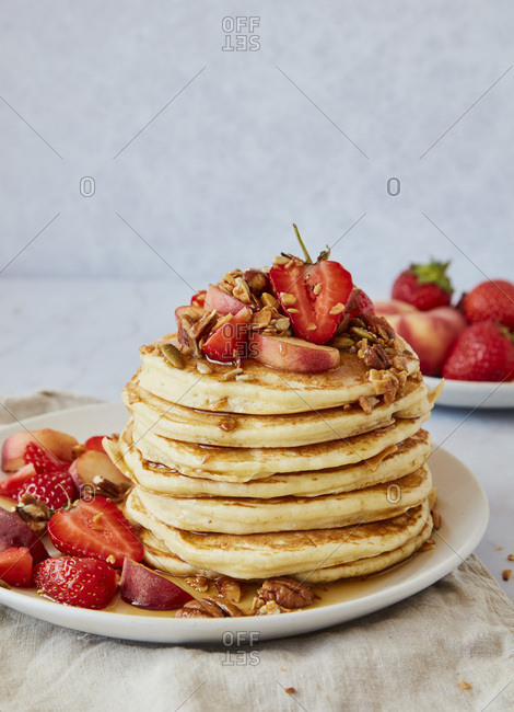 Stack of American Pancakes served with Strawberries, Peaches, Granola and Maple Syrup