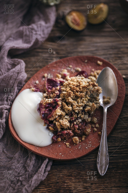 Plum crumble served with yogurt on a ceramic plate