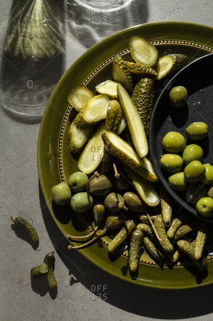 A selection of pickled gherkins, caper berries and green olives on an olive green plate. Shadows on the concrete background suggest glasses of wine.