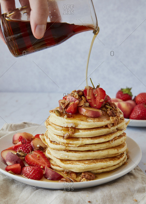 Pouring Maple Syrup Over A Stack of American Pancakes with Strawberries and Peaches