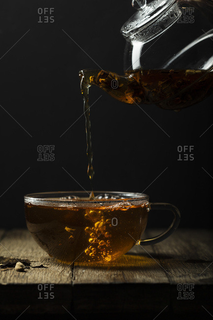 A refreshing cup of chai tea being poured from a glass teapot into a glass teacup. The surface is rustic timber.