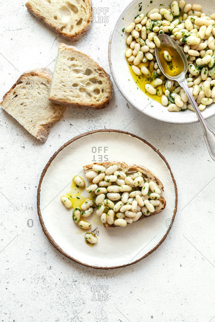 Creamy white bean salad with herb oil on a toast, top view