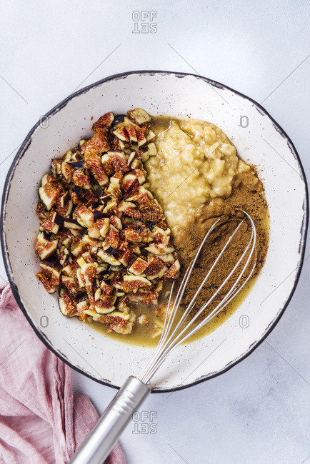 Mixing banana fig bread ingredients in a large ceramic bowl with a whisk inside