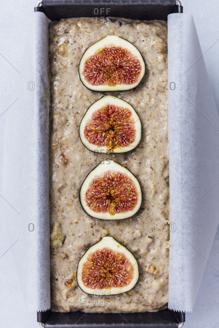 Vegan fig bread batter in a loaf pan topped with fresh figs