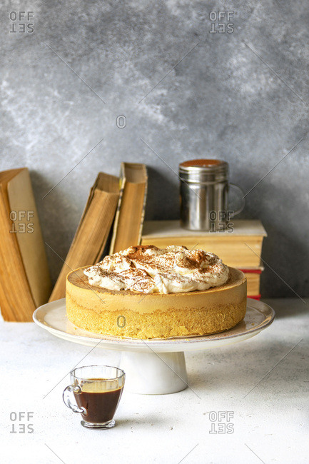No bake cheesecake on a cake stand and a cup of coffee on the table