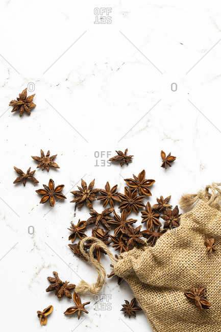 Star anise scattered from within a hessian bag.