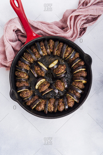 Oven baked meatball and eggplant casserole in an iron skillet photographed on a grey background