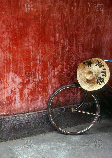 "Guangzhou, China - January 5, 2019: Bike in front of a red wall at a bus station, writing on hat says ""scenic south china"""